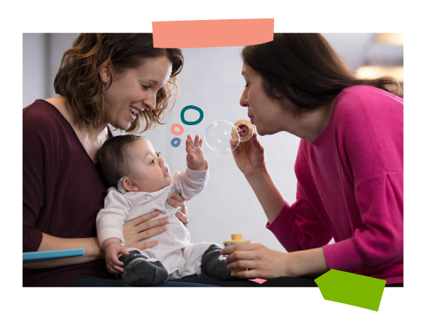 A mom blows bubbles toward her infant baby with hearing aids during an early intervention session.
