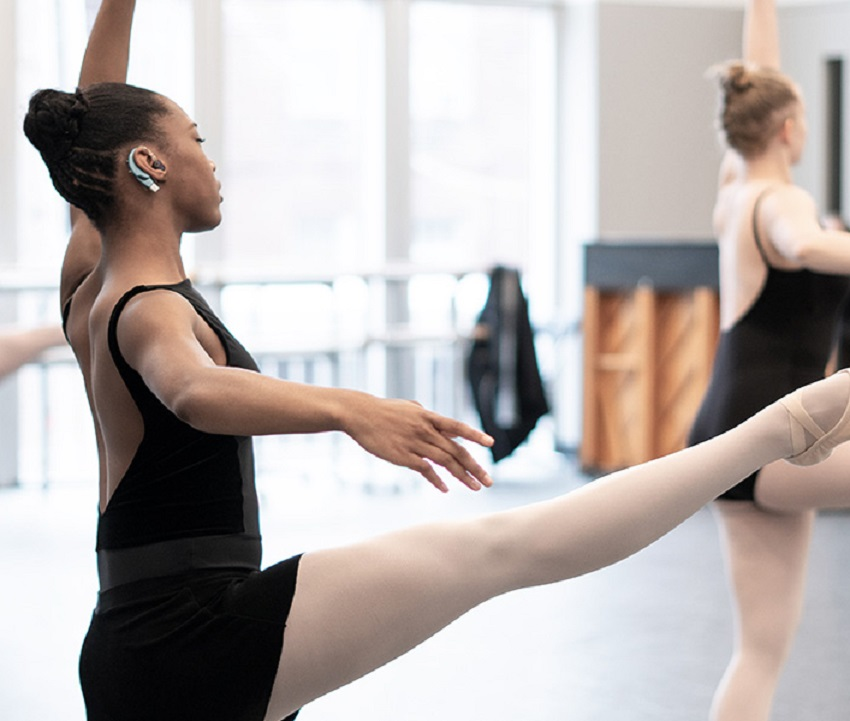CiCi practices ballet and listens to her dance teacher's instruction.
