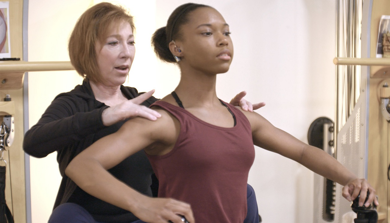 Video preview of CiCi practicing dance while her teacher corrects her form.