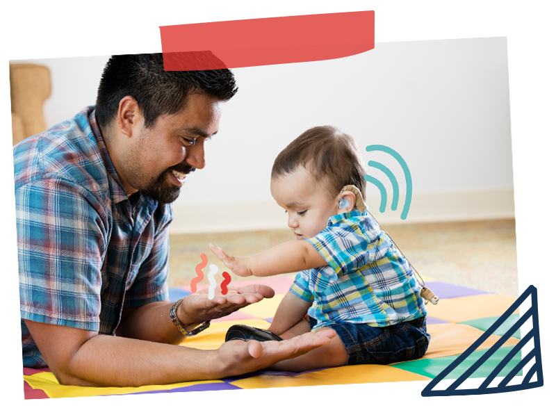 Dad and baby with hearing aids bond through playtime.
