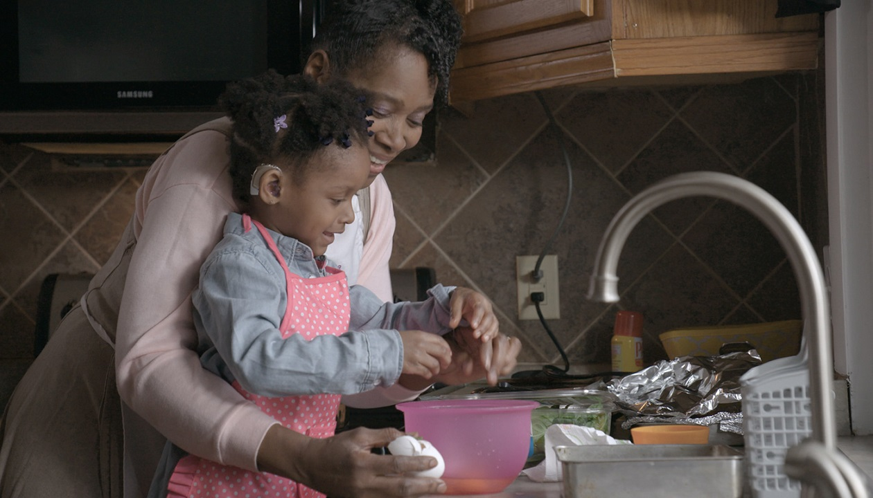 Video preview of Corlena helping her grandmother cook in the kitchen.