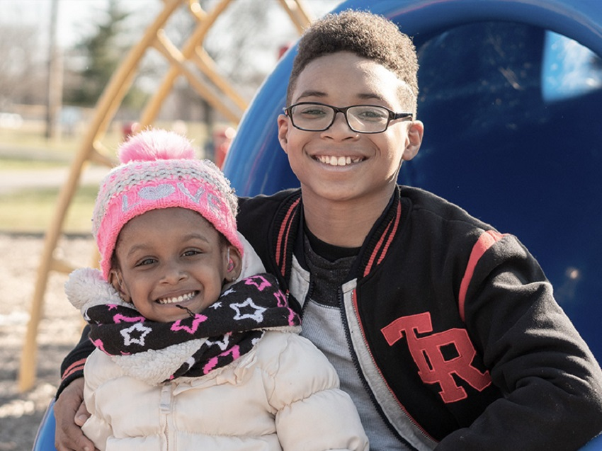 Corlena and her brother Cayden smile at the camera while playing at the neighborhood park.