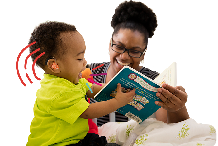 Mom laughs holding a book with her toddler son with hearing loss.