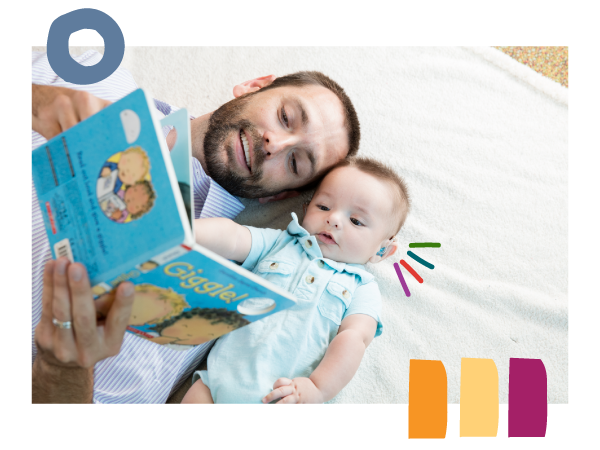 Dad reads a book aloud to his infant son wearing hearing aids.