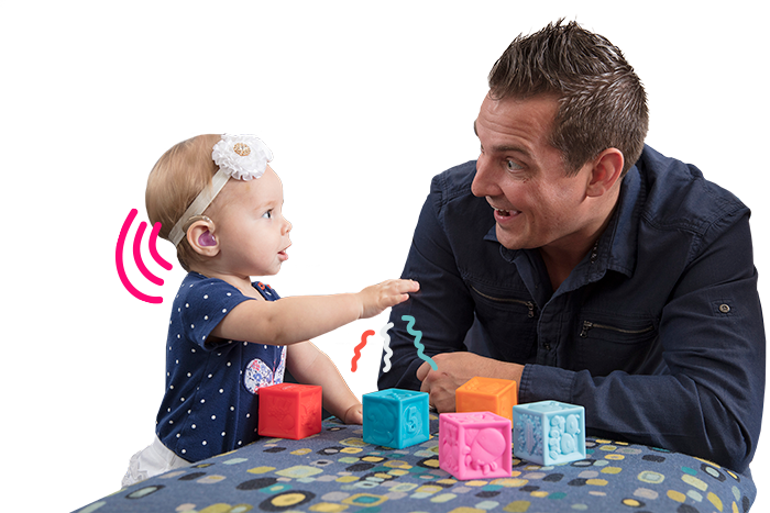Dad and young daughter with hearing aids play together.