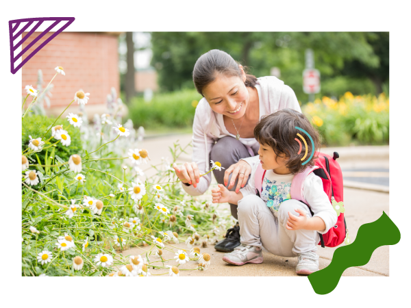 A mom and her preschool daughter with hearing loss look at a flower.