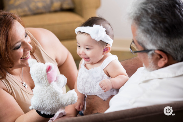 Parents hold a puppet up to their smiling baby wearing hearing aids.