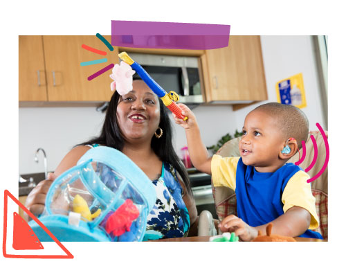 Little boy with hearing aids plays with fishing toy while mom watches and smiles.