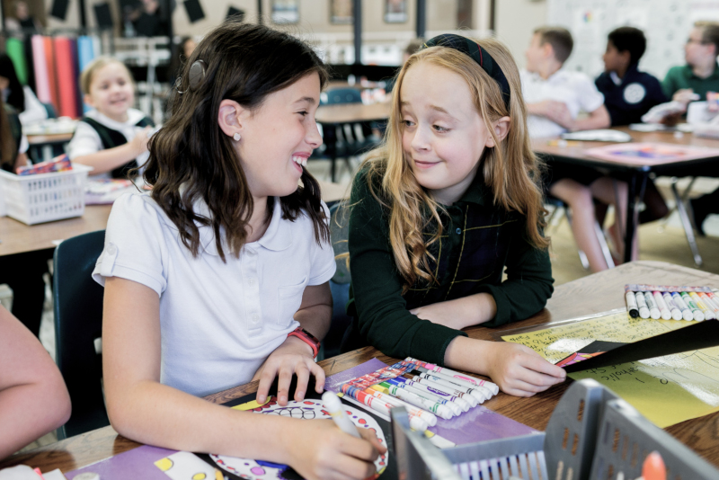 Maggige laughs with a friend while coloring a picture in art class.
