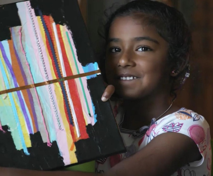 Maya smiles while holding a piece of her art up.