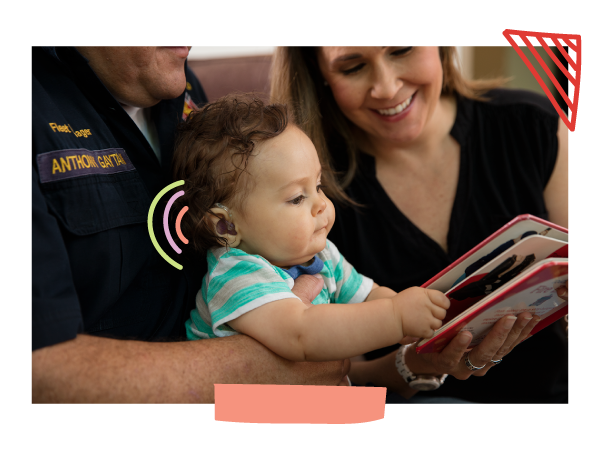 A little baby with hearing aids hold a book as his parents read aloud to him.