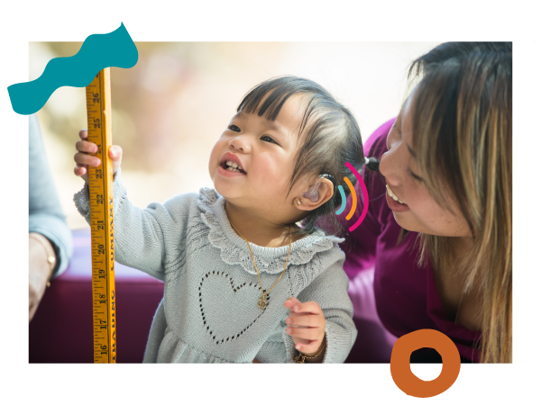 Little girl with hearing aids smiles holding a yard stick with smiling mom.
