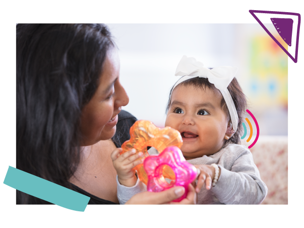 A baby with hearing aids plays with a colorful toy with her mom.