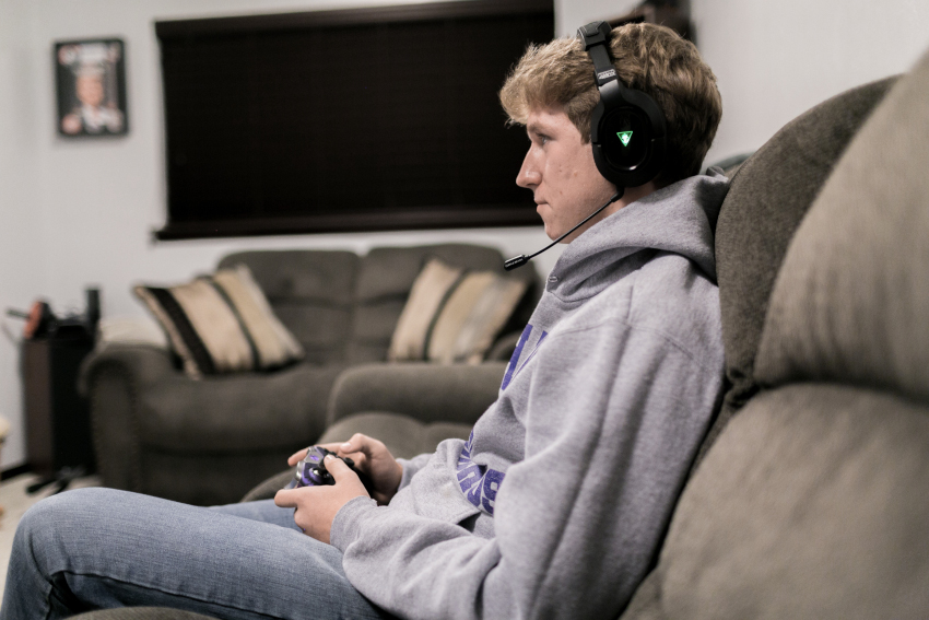 Zach wears headphones to hear his video game.